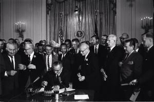 """President Lyndon B. Johnson signs the 1964 Civil Rights Act as Martin Luther King, Jr., and others, look on."""", 2 July 1964, Cecil Stoughton, White House Press Office (WHPO)"""
