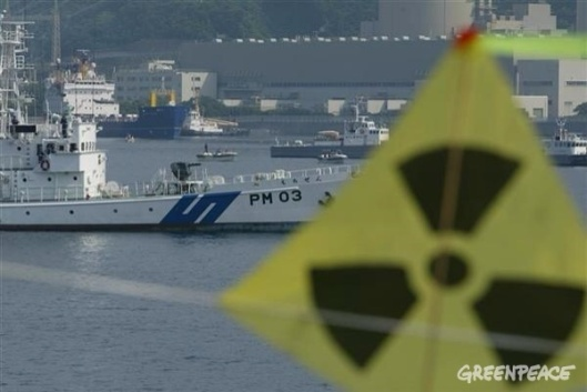Image: Military ship and MV 'Pacific Pintail' in front of Takahama Nuclear Power Plant in Uchirua Bay, Japan. Surrounded by Japanese police and coastguard, Greenpeace activists in inflatables protested in Uchiura Bay. The protest addressed the BNFL ship 'Pacific Pintail' departing after being loaded with rejected weapons-usable Plutonium Mox fuel being shipped back to the UK. 07/04/2002 © Greenpeace/Jeremy Sutton-Hibbert