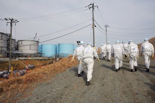 IAEA Mission Team (02110045)  walking by water tanks Fuku 1 February 2015. Photo Credit: Susanna Loof / IAEA