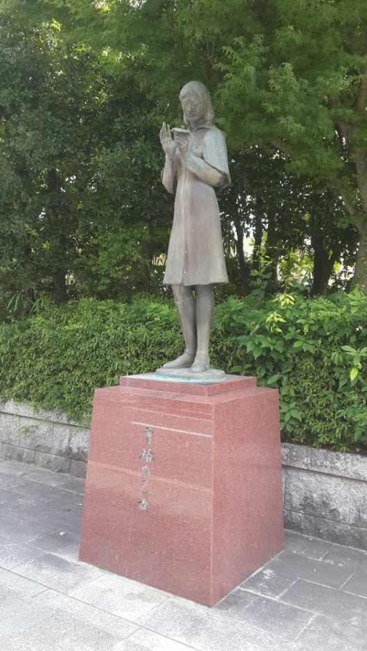 Memorial Statue of Sadako Sasaki outside the Noborichō Junior High School in Hiroshima, Japan. Noborichō was her Jr. High school, Photo by Chenmingyu, CC-By-SA, via wikimedia
