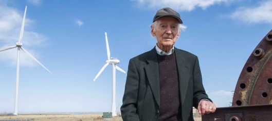 NREL Senior Engineer Palmer Carlin at the National Wind Technology Center, flanked by some of the massive turbines he says early wind technology pioneers only dreamed of seeing. Photo by Dennis Schroeder NREL