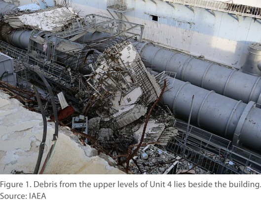 Figure 1. Debris from the upper levels of Unit 4 lies beside the building. Source: IAEA via NASA