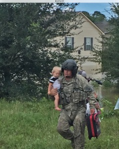 Sgt. Chad McCann of Deville, Louisiana, crew chief with F Company, 2-135th MEDEVAC, brings a young child to the waiting UH-60 Blackhawk to be taken to safety after flood waters threatened his home in South Louisiana, Aug. 15, 2016. More than 3,880 Louisiana National Guardsmen are still engaged in flood response efforts, to include rescues, evacuations, security patrols, engineering missions, and commodities distribution. (Photo Credit: Chief Warrant Officer 3 Jesse Curtis)