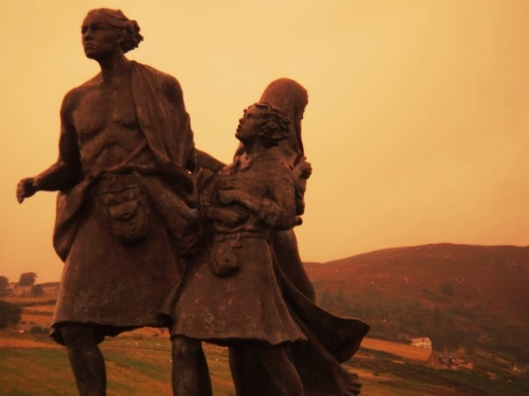 The Emigrants statue in Helmsdale, Scotland, surrounded by mist at the base of the Highland Mountains, red enhanced
